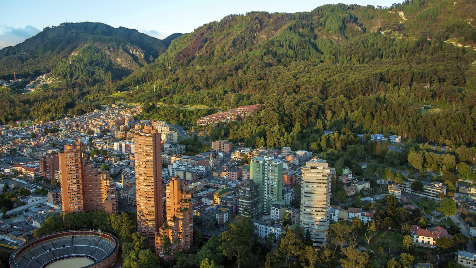 Aerial view of Bogota city high rises, houses and dome sports field on sunny day