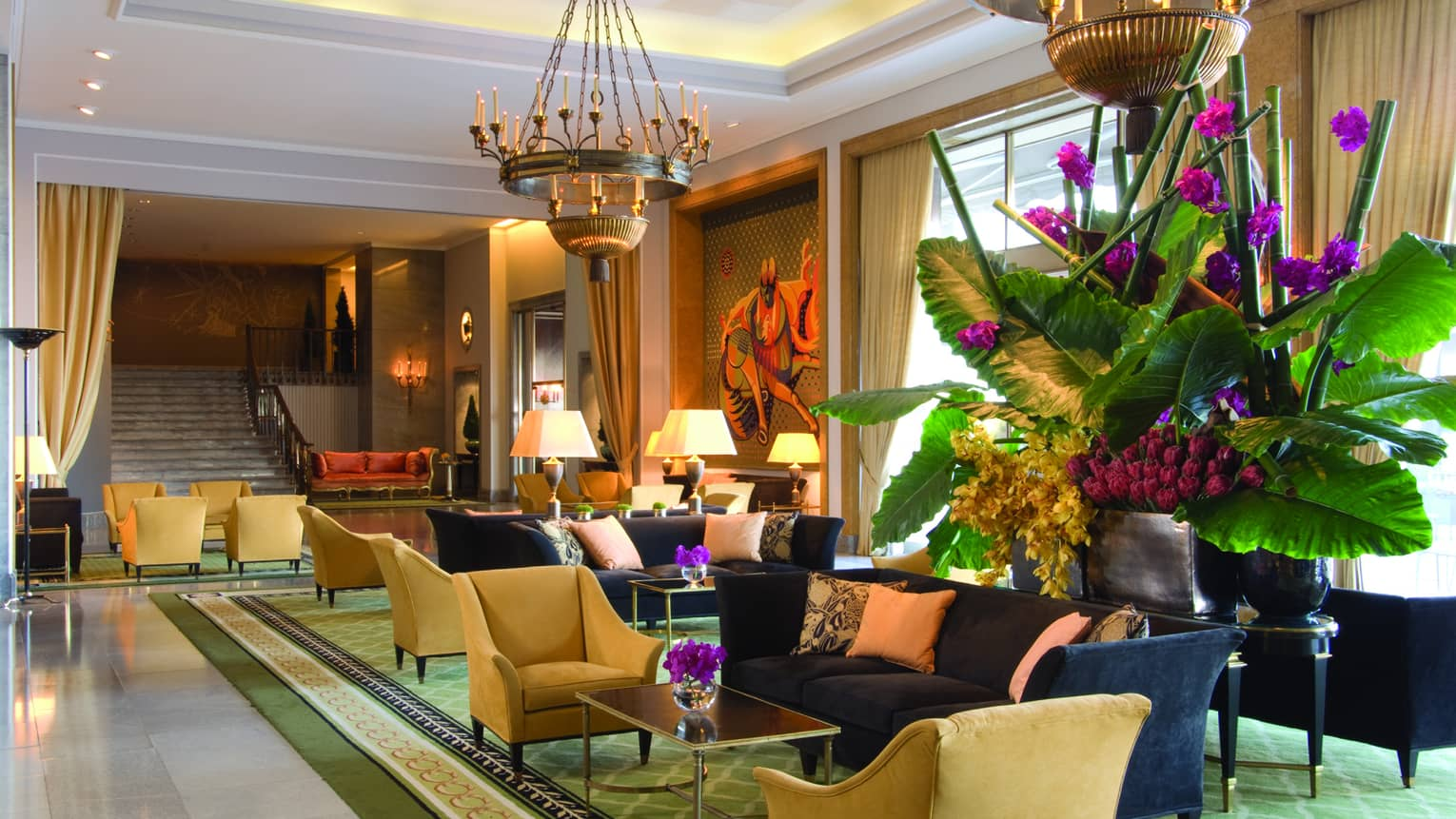 Sunny hotel lobby with blue sofas, yellow armchairs, large tropical plant with purple flowers