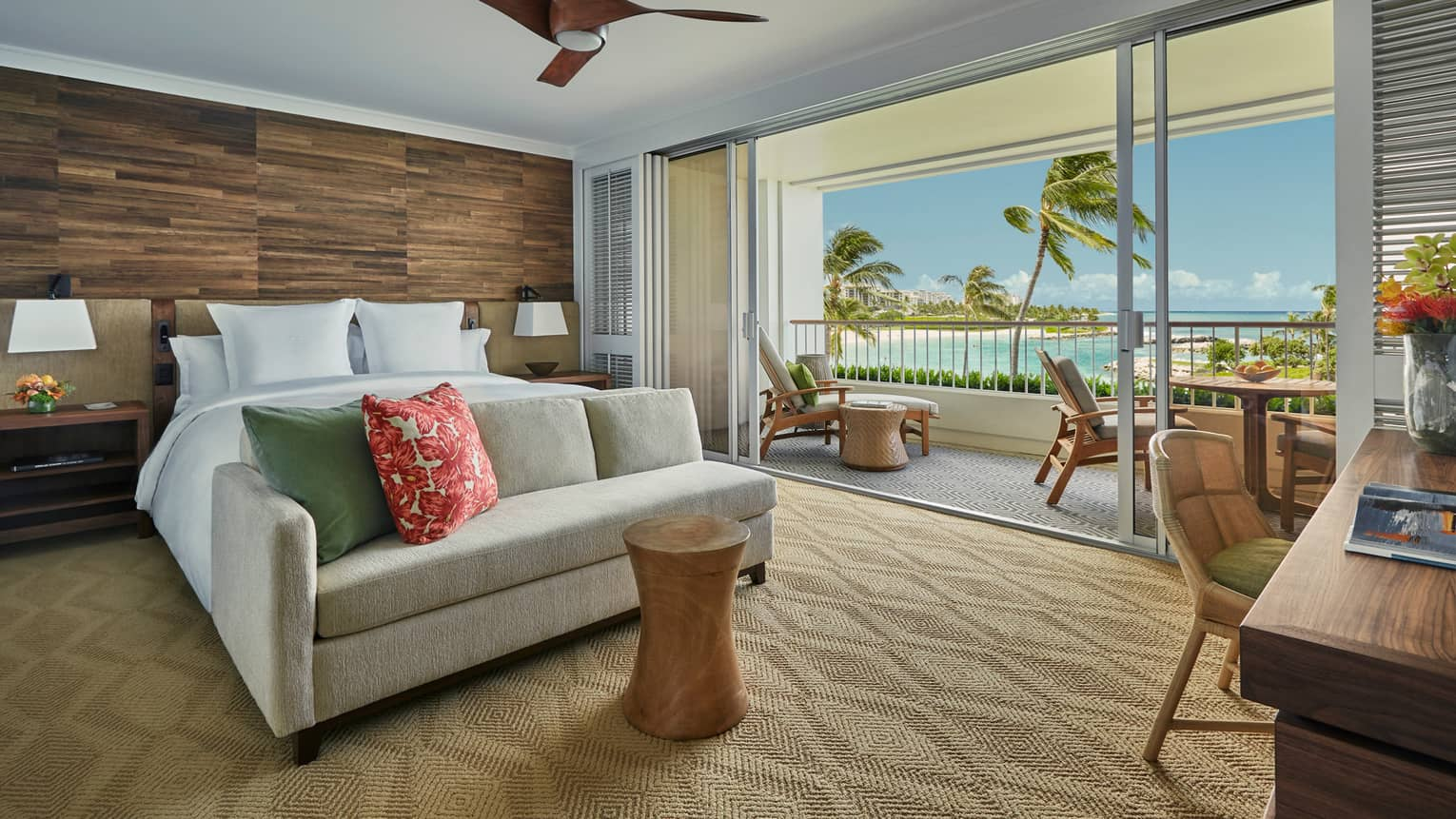 Prime Corner Oceanfront Room loveseat at foot of bed against wood grain wall, balcony wall