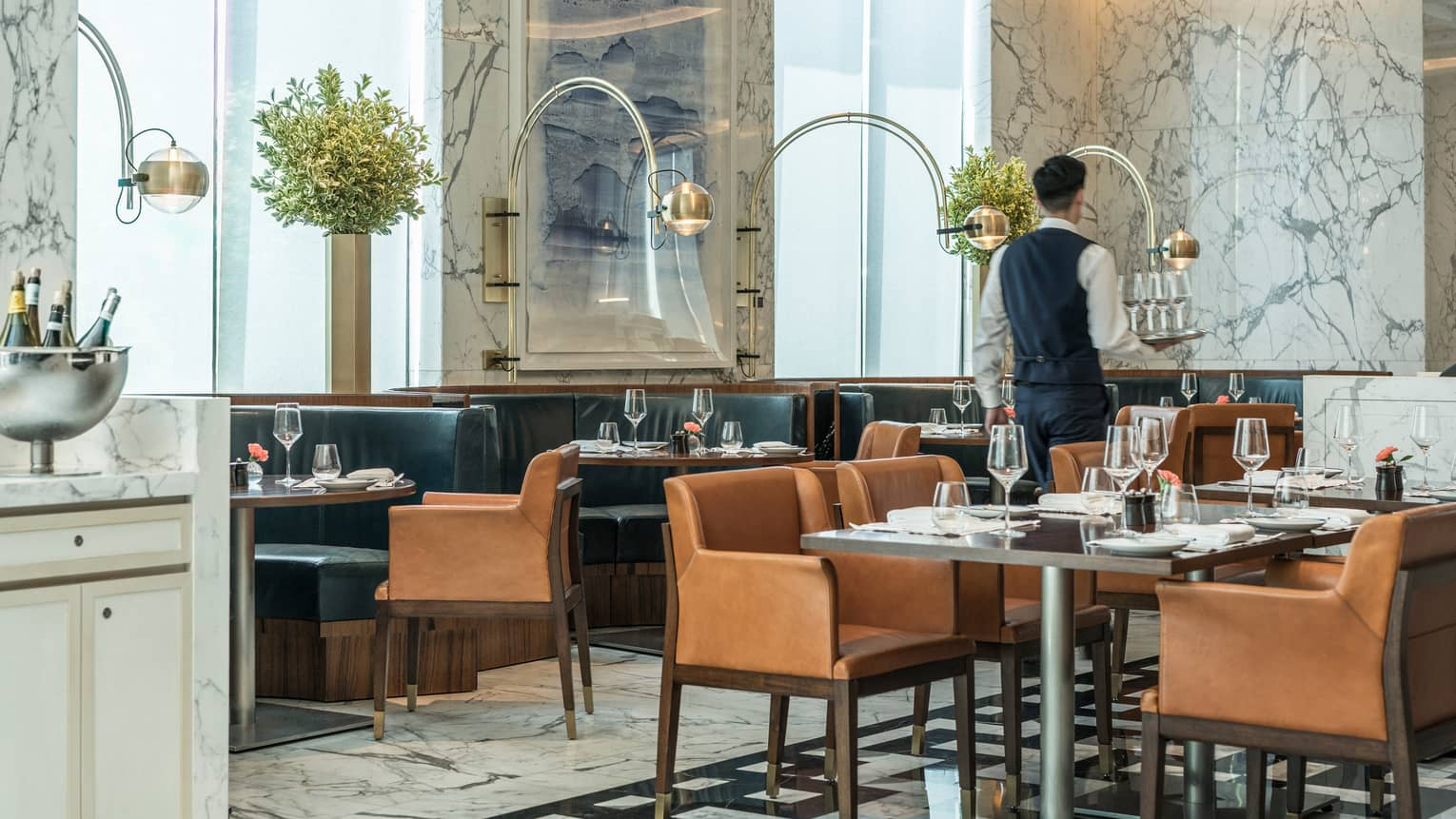 Server carries tray of glasses past lounge tables, chairs in Boccalino dining room