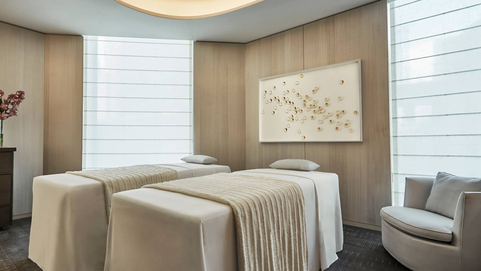 Side-by-side massage tables with white blankets in spa room