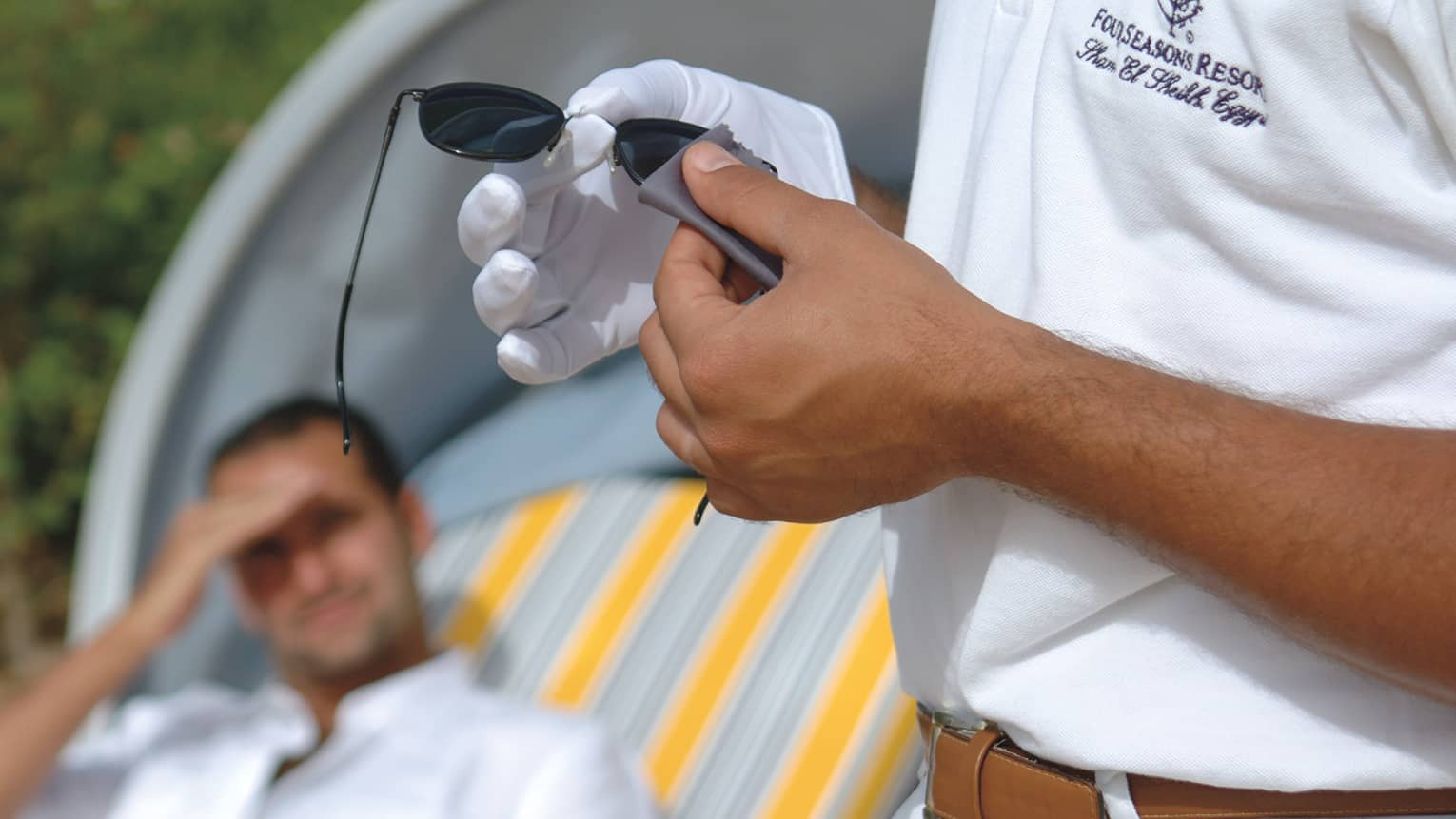 Close-up of hands, one with white glove, cleaning black sunglasses