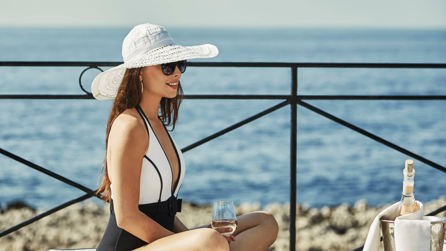 Woman wearing swimsuit, white sun hat, sunglasses sits cross-legged with wine