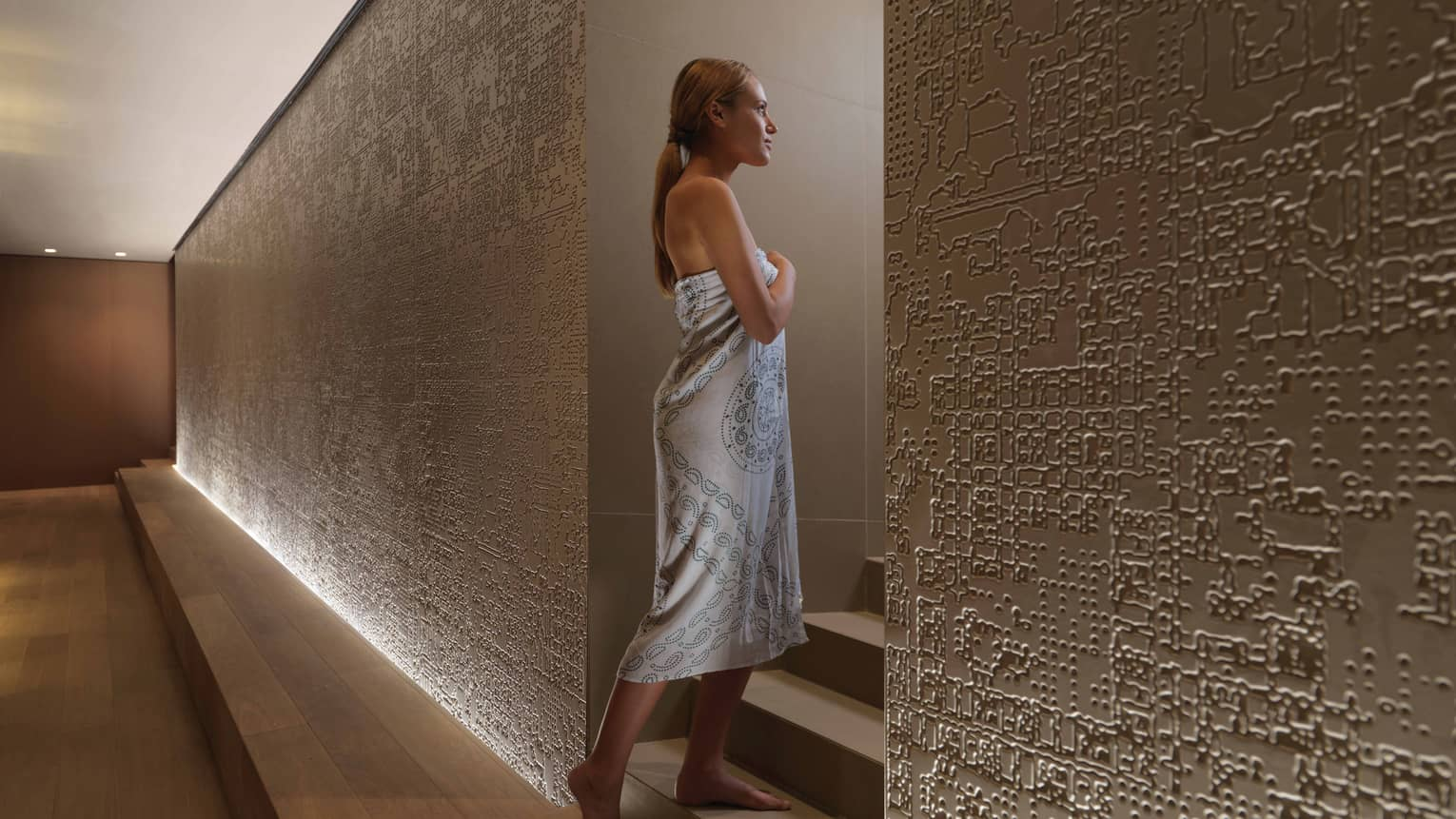 Spa tile walls, woman wrapped in white towel walks up steps to steam room