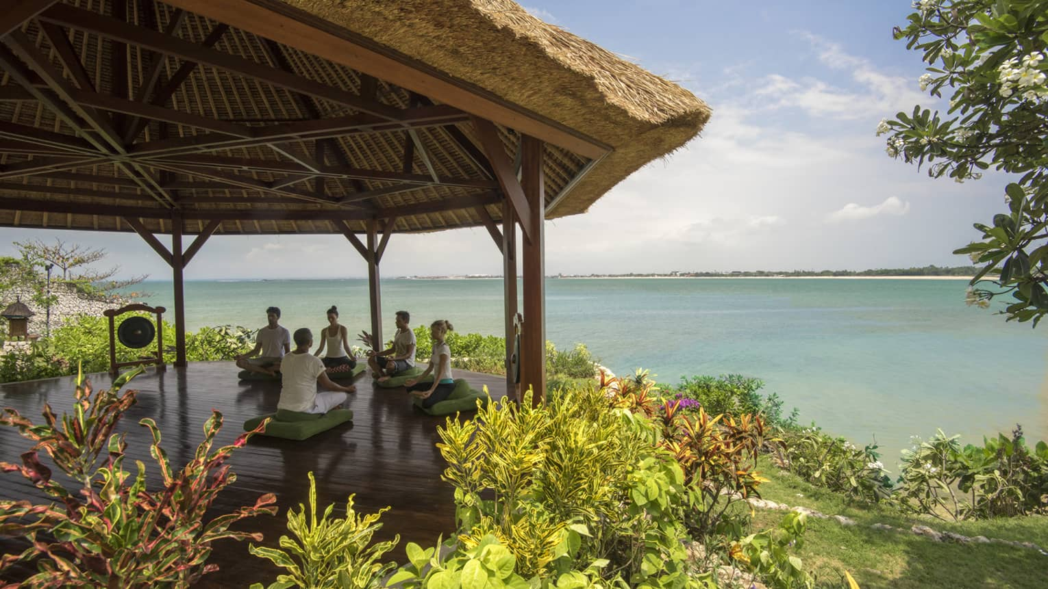 Five people sit cross-legged meditating on green cushions under thatched-roof gazebo by ocean