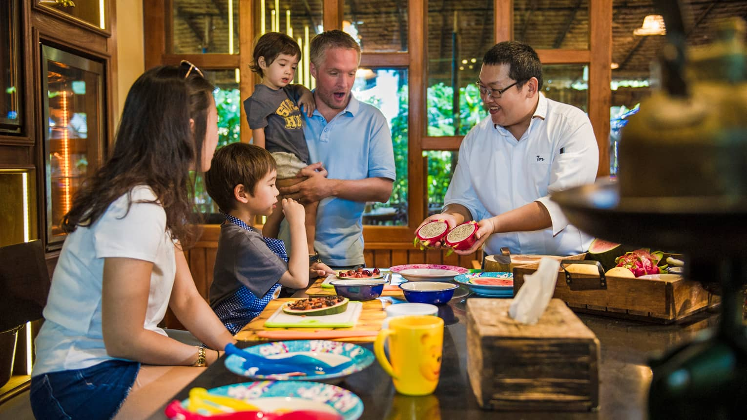 Chef presents two halves of dragon fruit to family during Thai cooking demonstration