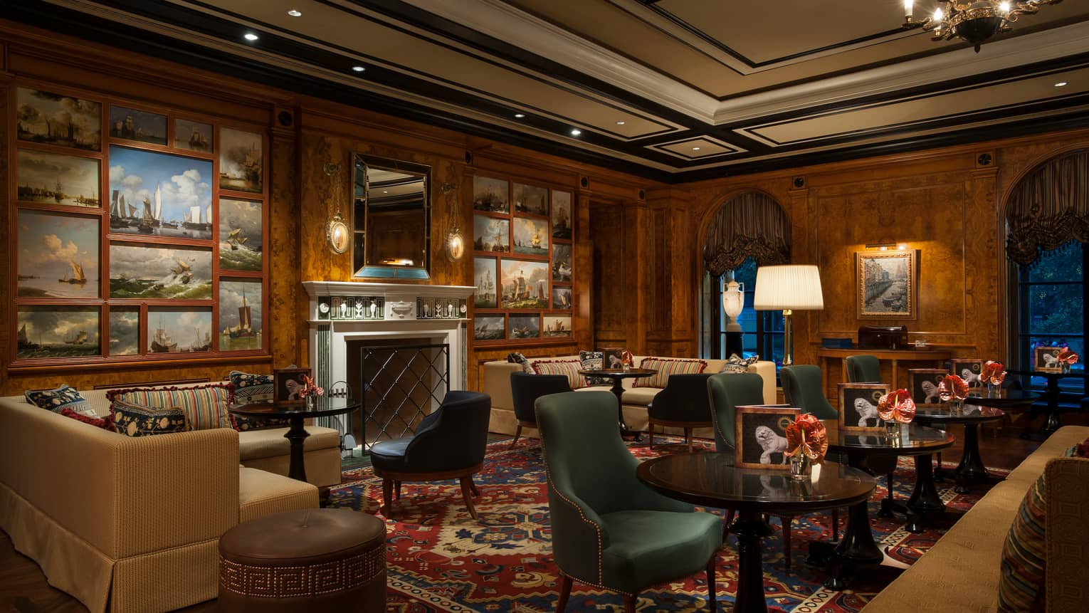 Xander Bar lounge with sofas, green velvet chairs, murals of sailboats around fireplace mantle