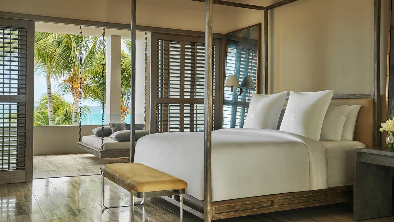 Bed with white linens, rustic wood canopy, small leather bench, open patio door shutters  to hanging chair