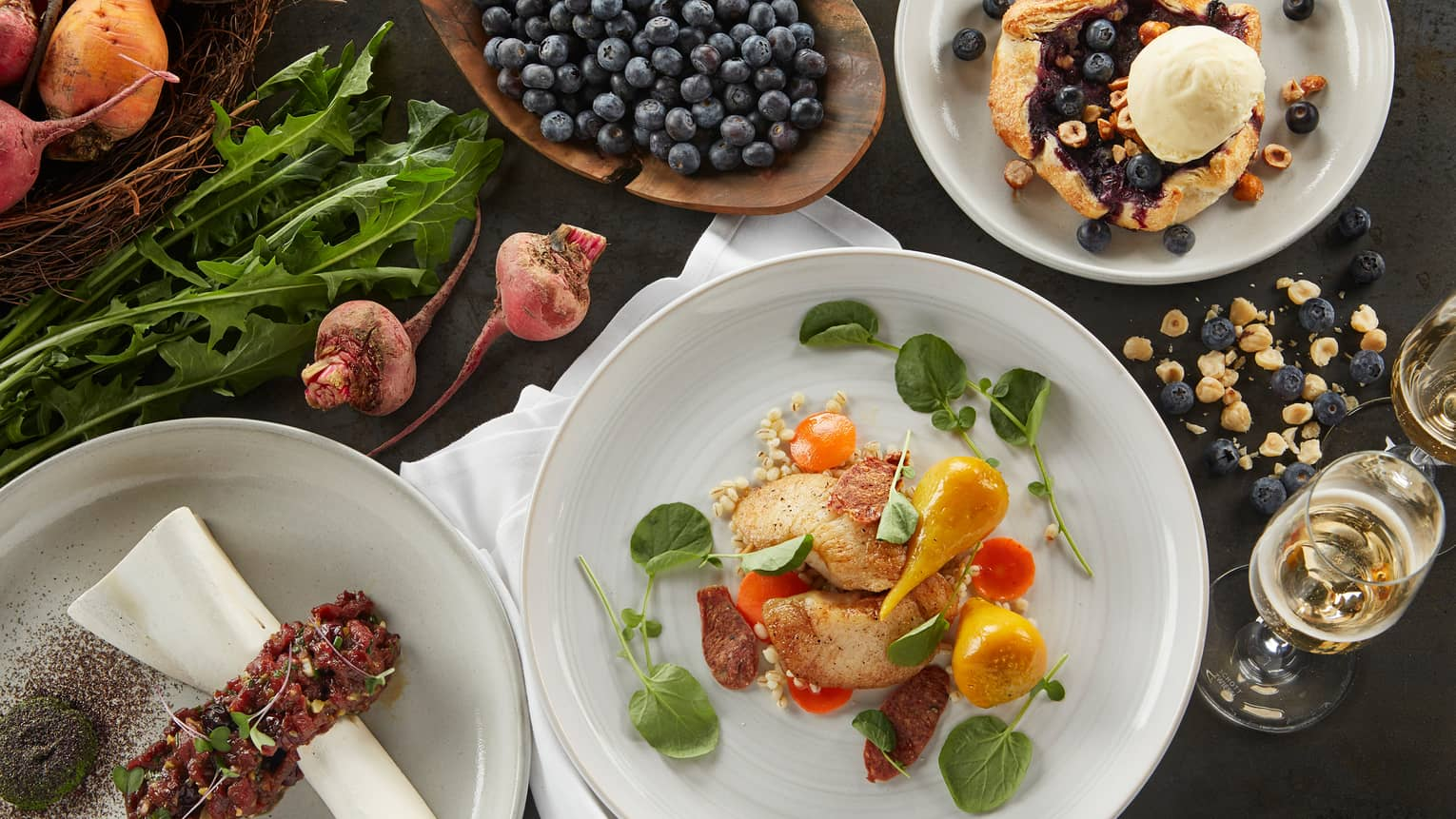 Aerial view of dinner plate with roast chicken and vegetables, blueberry crumble with cream, fresh berries