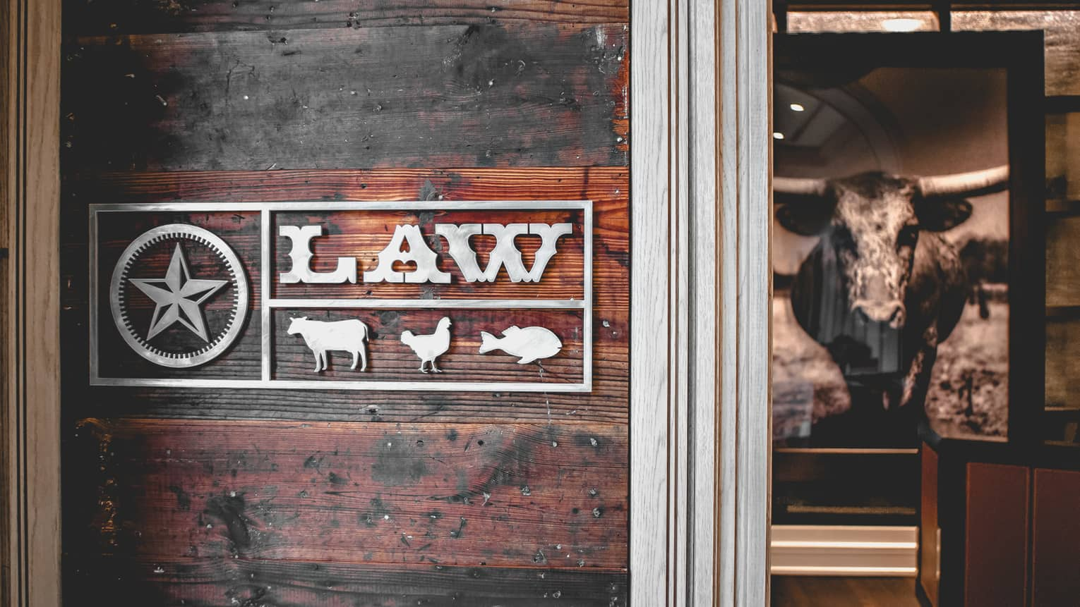 Law restaurant sign with metal Texas lonestar, cow, chicken and fish symbols against rustic wood wall