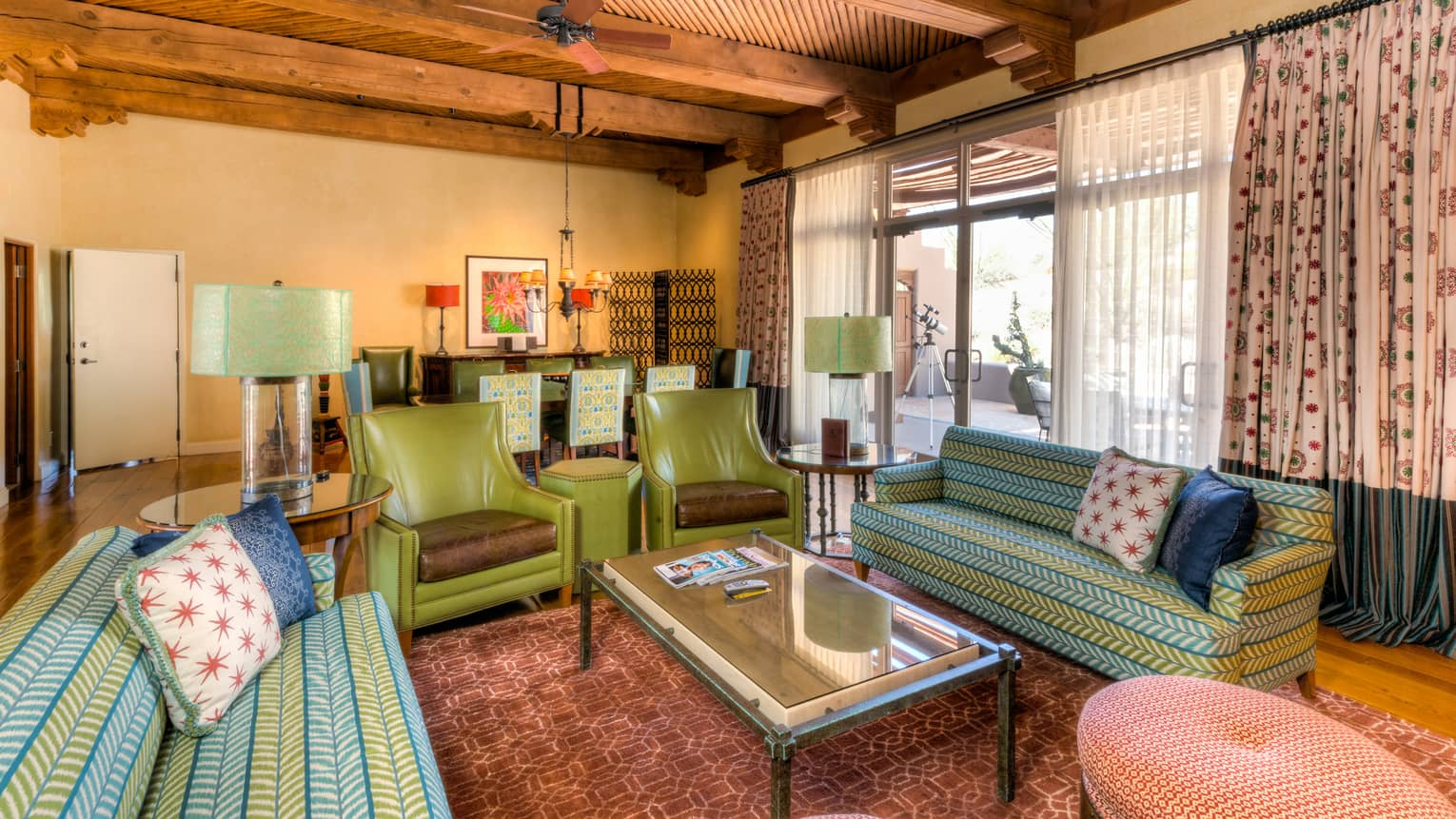 Pinnacle Three-Bedroom Suite with blue-and-green sofas, armchairs, coffee table, floor-to-ceiling windows