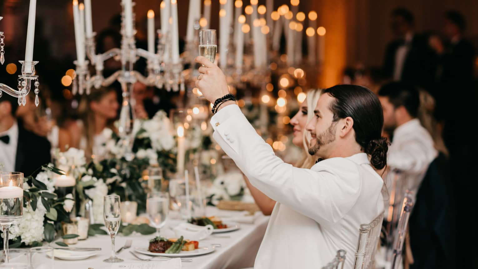 Wedding guests raise glasses during toast at candlelit banquet table