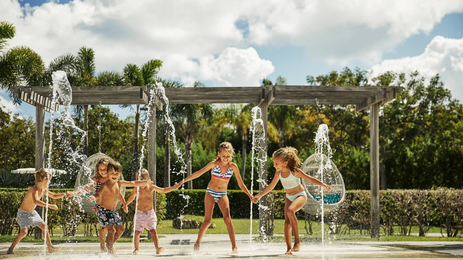 Group of young children in swimsuits runs across outdoor splash pad with fountains