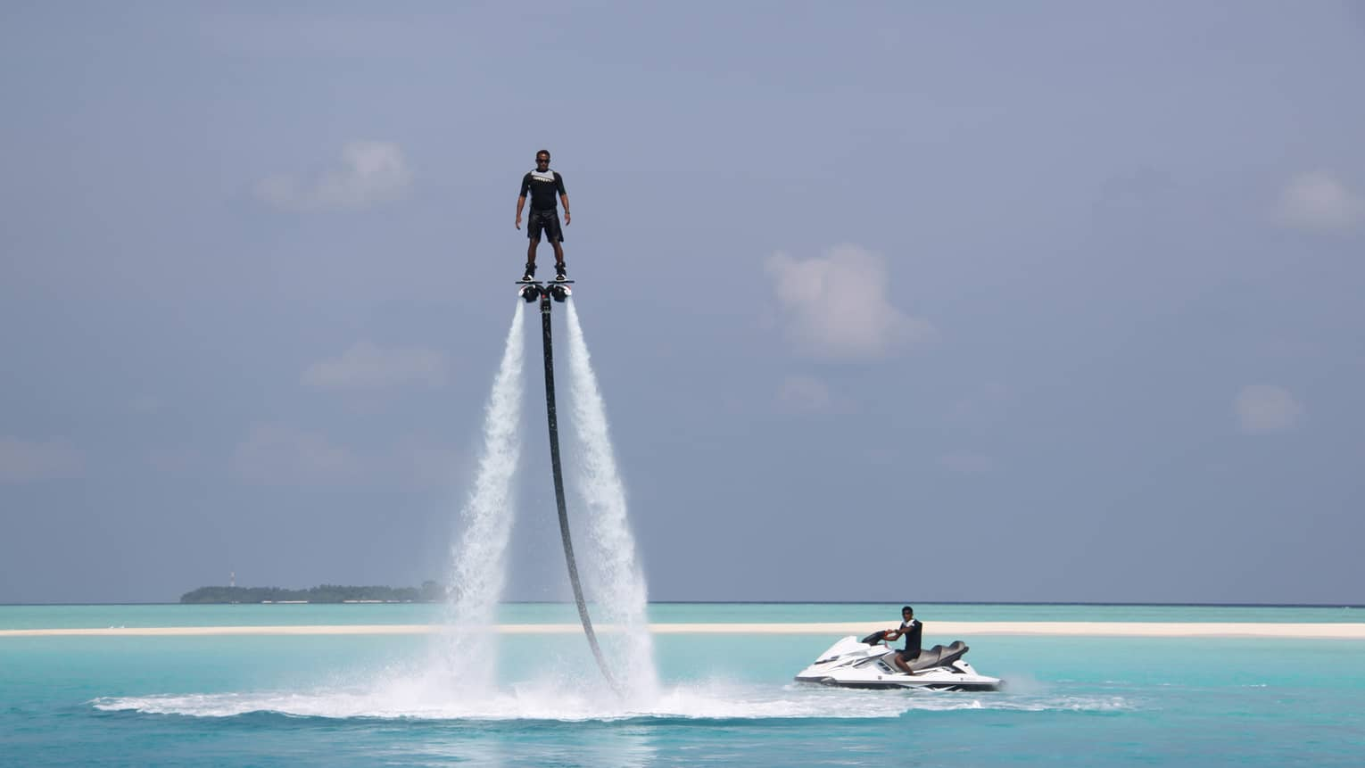 Person hovers suspended in air above ocean on X Jetblade pack, near jetski