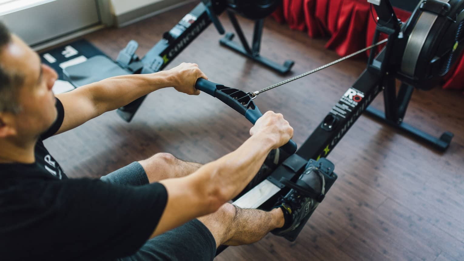 Man sits, pulls handle of cardio rowing machine in fitness facility