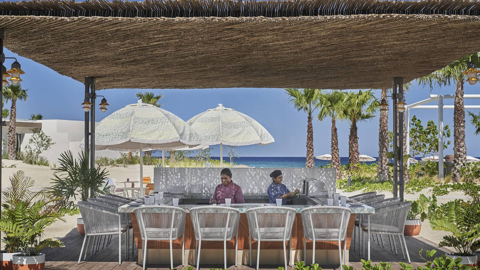 Two staff members behind beach bar with thatched roof, white rattan chairs, water view