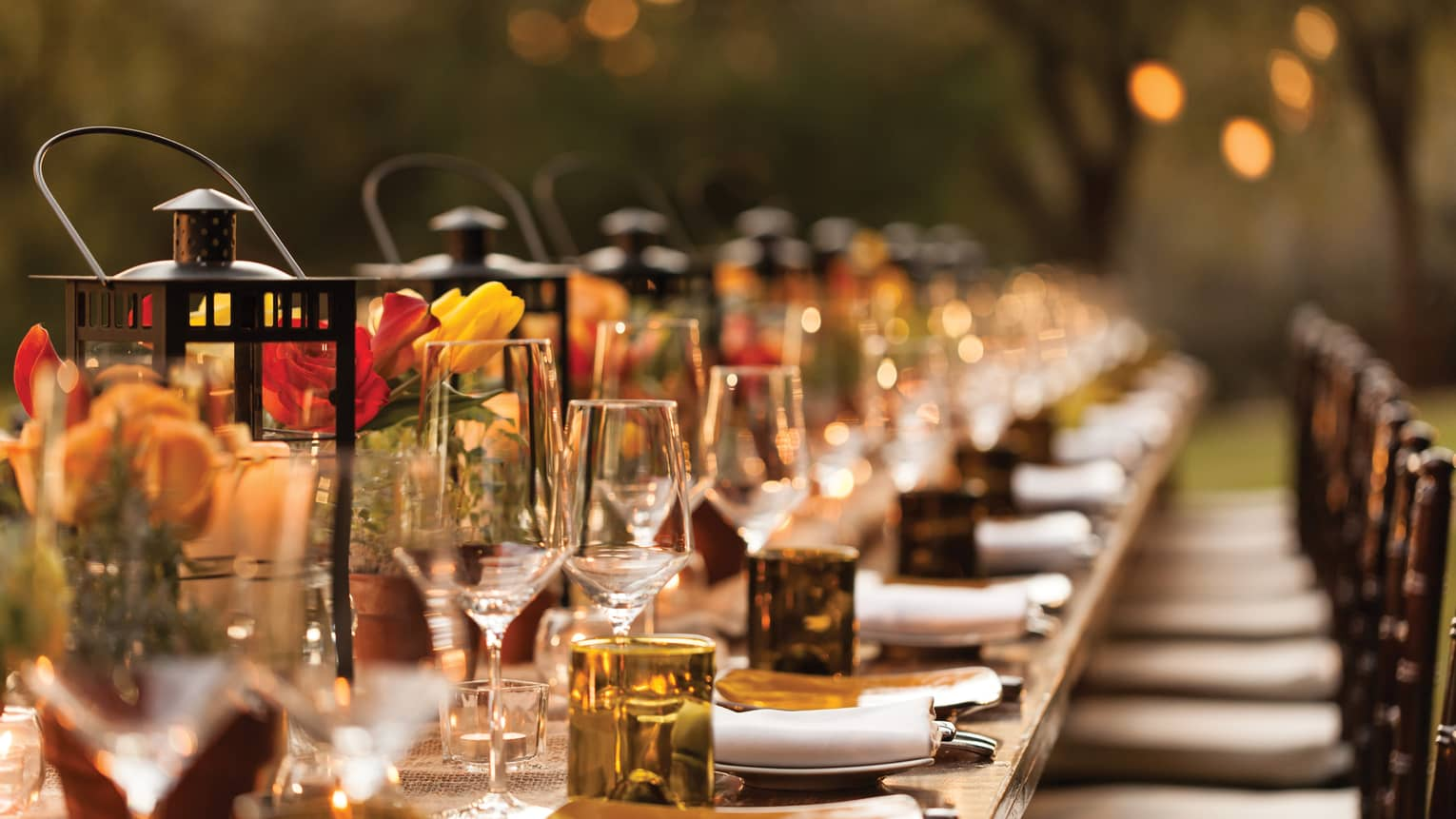Close-up of long banquet table with red and yellow flower, amber glassware