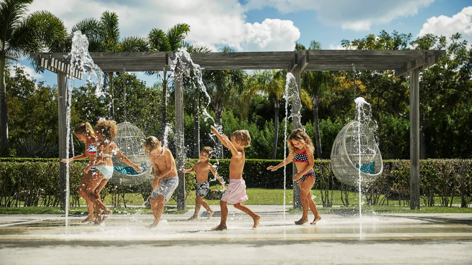 Kids in swimsuits laugh and run under outdoor splash pad, fountain
