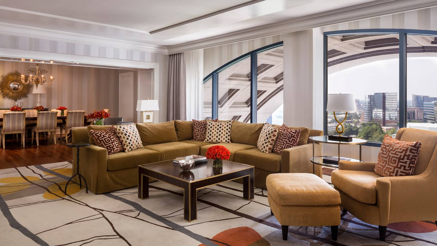 Presidential Suite gold L-shaped sofa, armchairs, dining room by large picture window