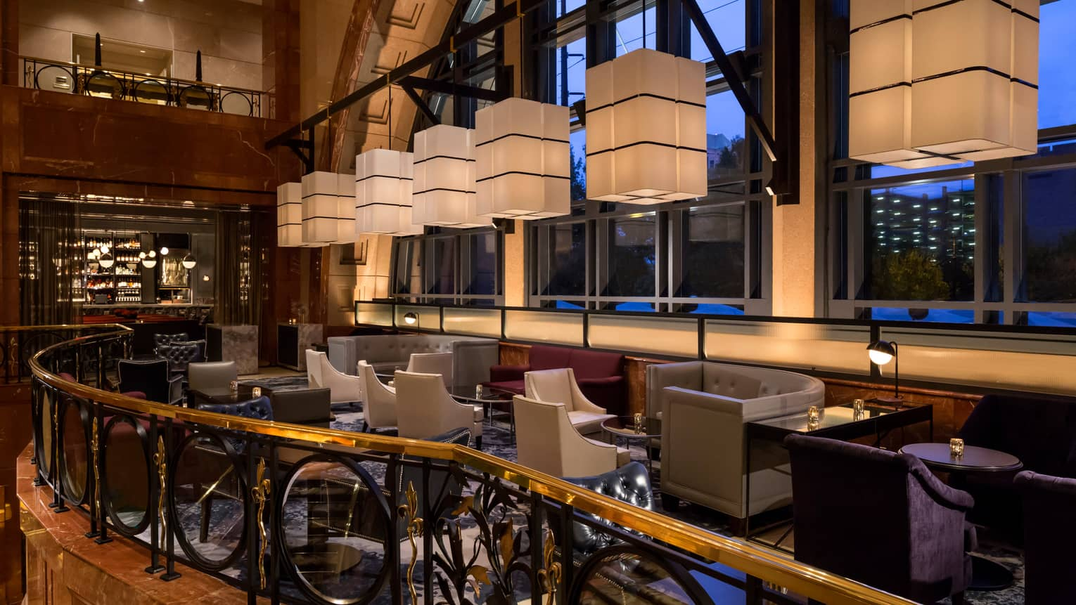 White rectangular lanterns hang above Bar Margot lounge area in front of arched window