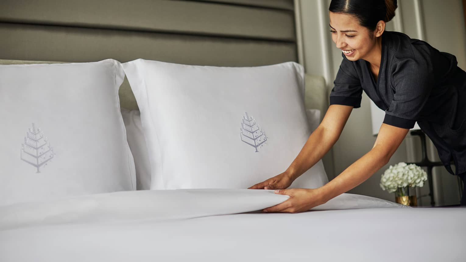 Hotel housekeeper smooths blanket under bed pillows with embroidered Four Seasons logos