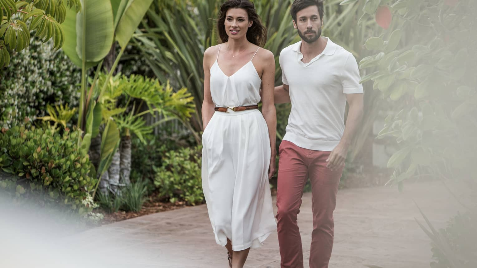 Man and woman in casual summer clothes stroll down path surrounded by tropical plants