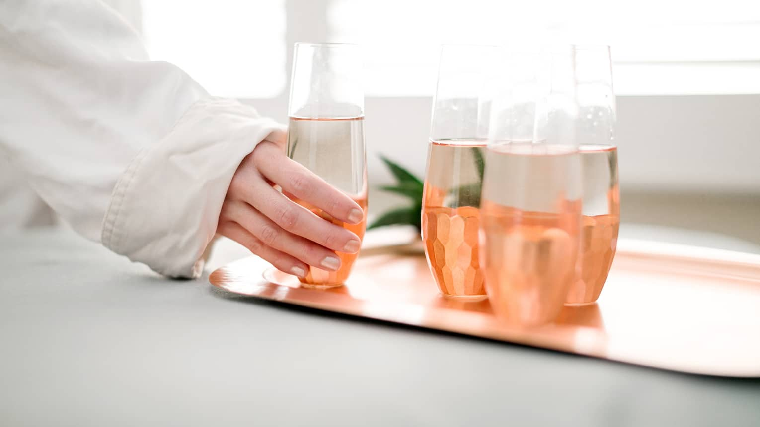 Woman in white bathrobe hand reaches for glass of water, next to three glasses on rose gold tray