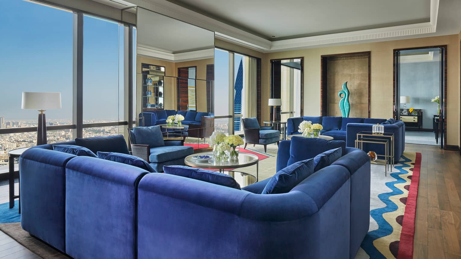 Royal Suite large u-shaped blue plush sofa, multiple seating areas, window with Bahrain city views
