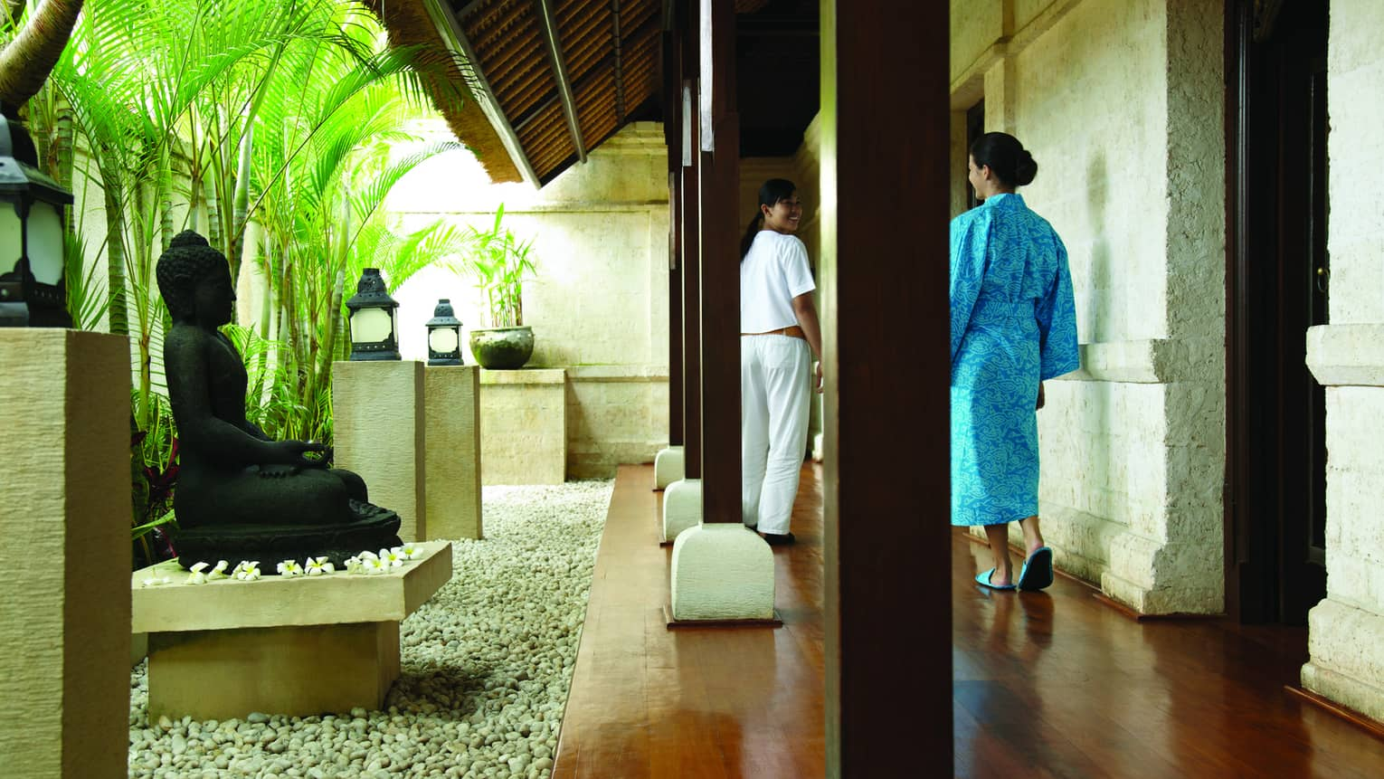 Woman in blue robe walks down hallway past black Buddha statue, rock garden