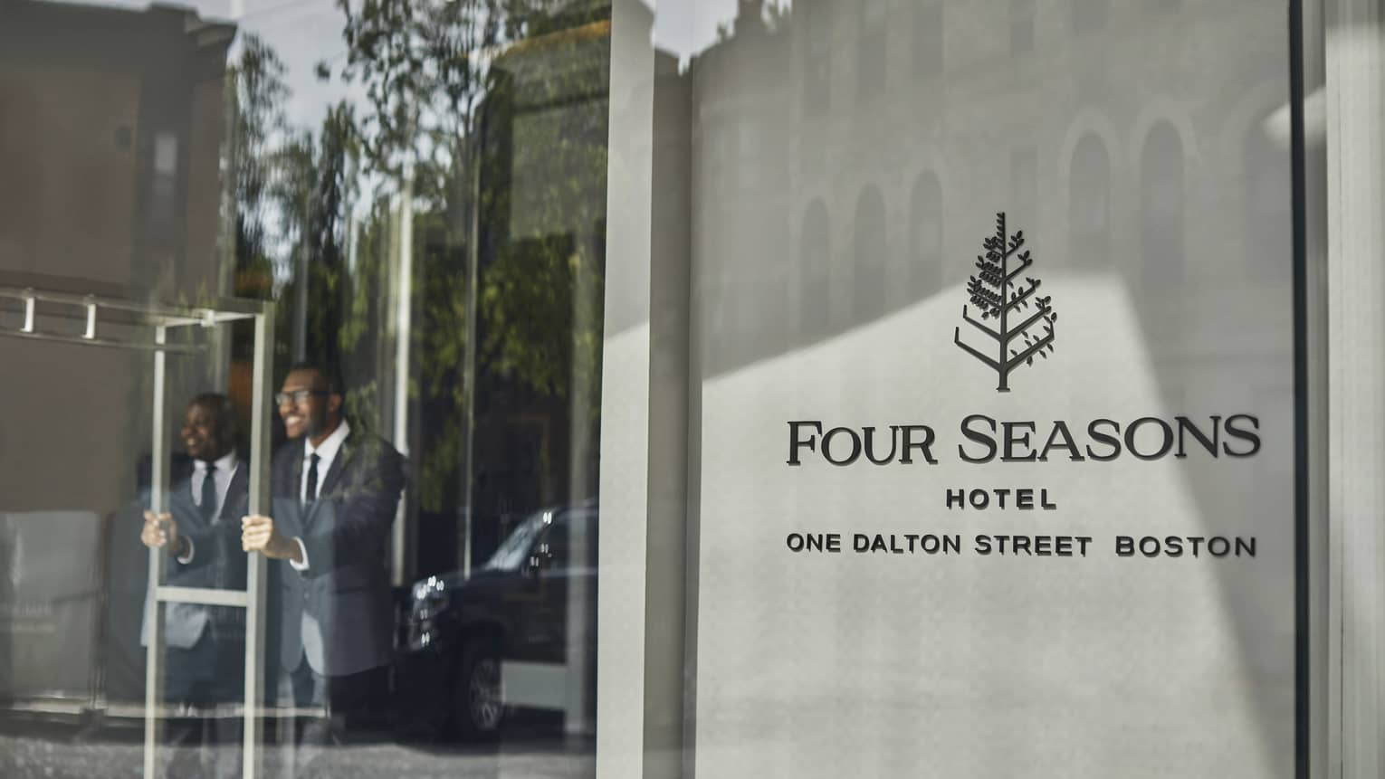 Four Seasons staff open the entrance door for guests