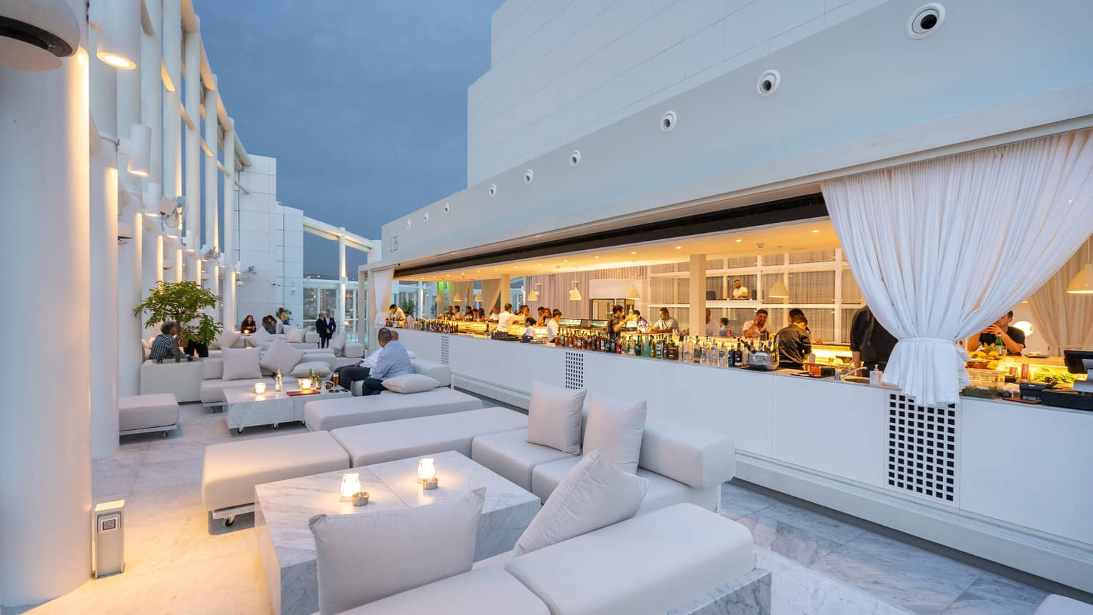 All-white contemporary furniture and decor with ambient lighting at rooftop lounge