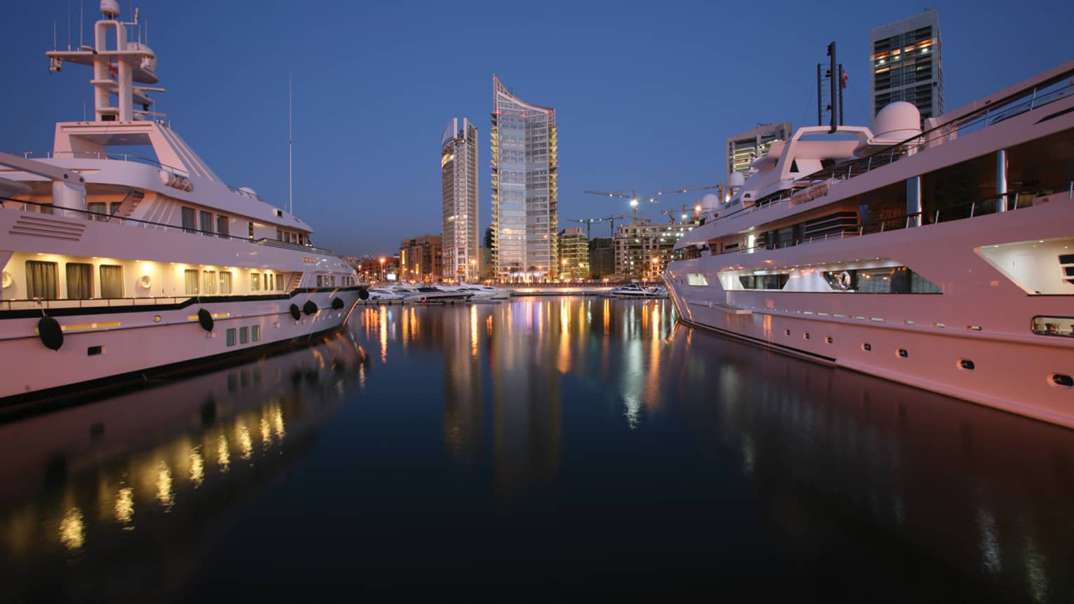 High rise buildings with lights at night reflected on water between two white yachts