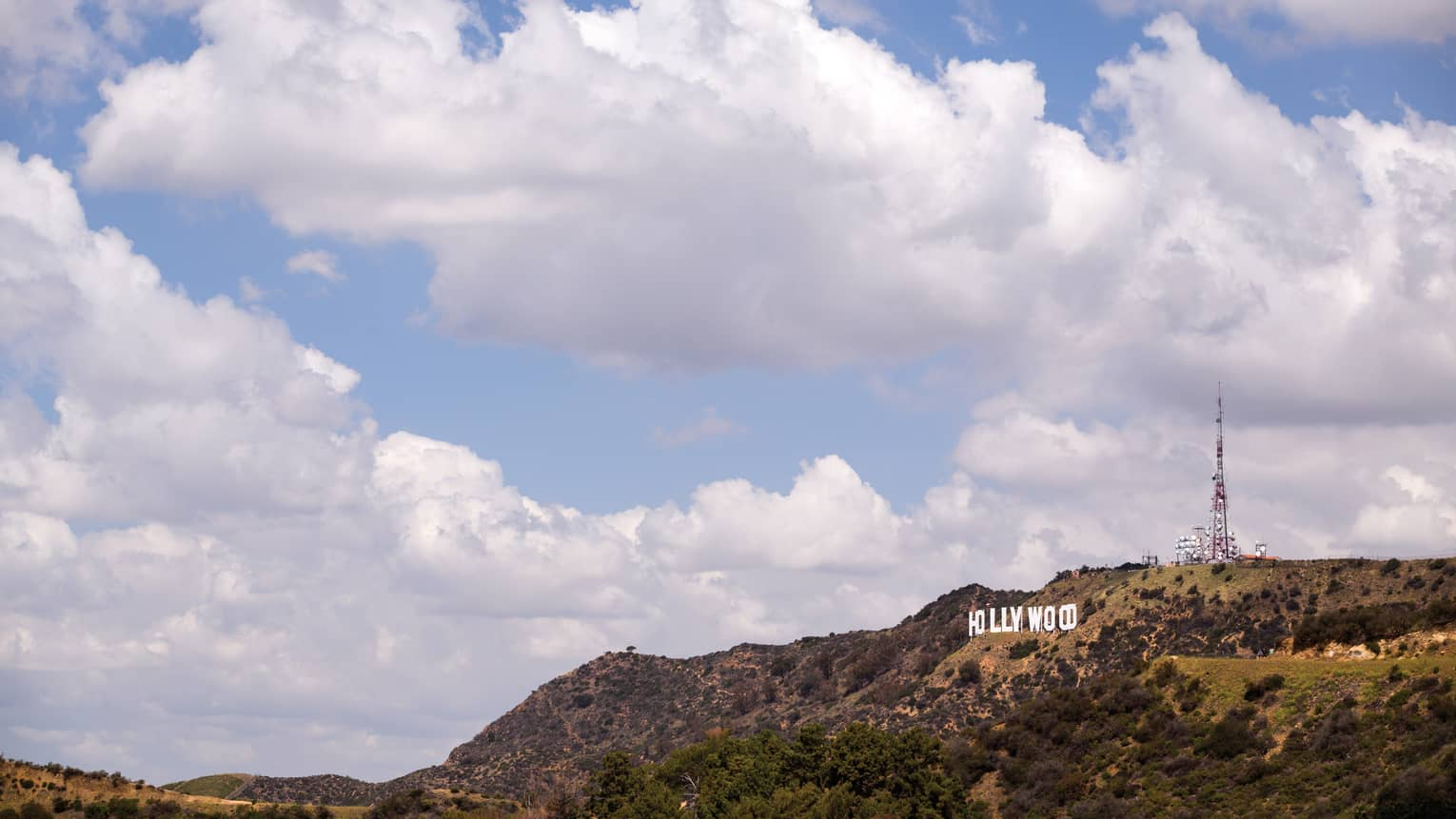 Hollywood sign on green Los Angeles hills against blue sky