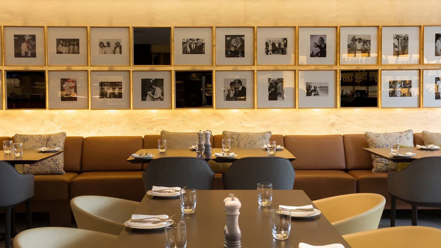 Nemo restaurant dining tables with brown banquette, bucket chairs, black-and-white framed photos arranged on wall