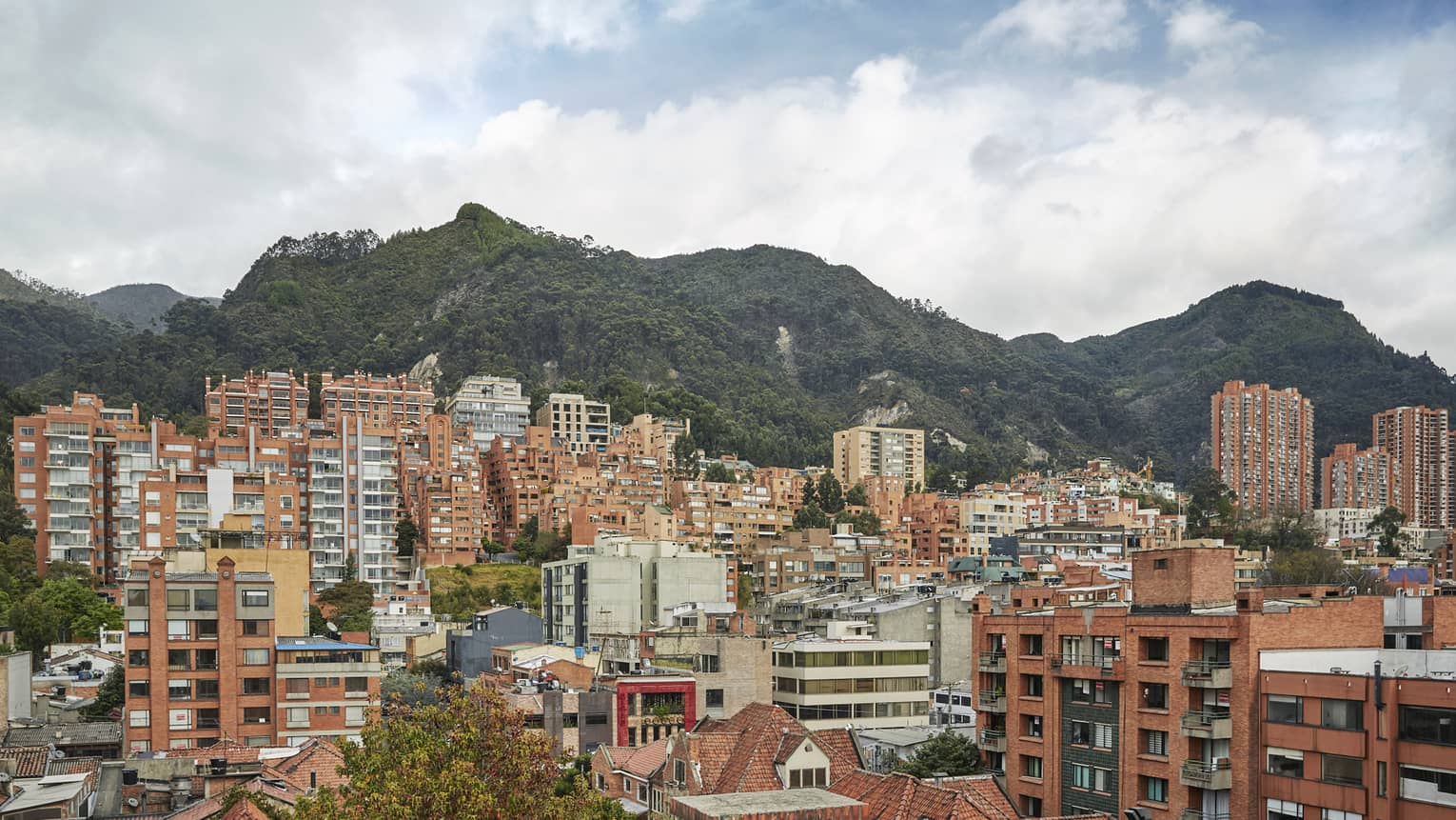 View of Bogota city skyline with buildings in front of tall mountains
