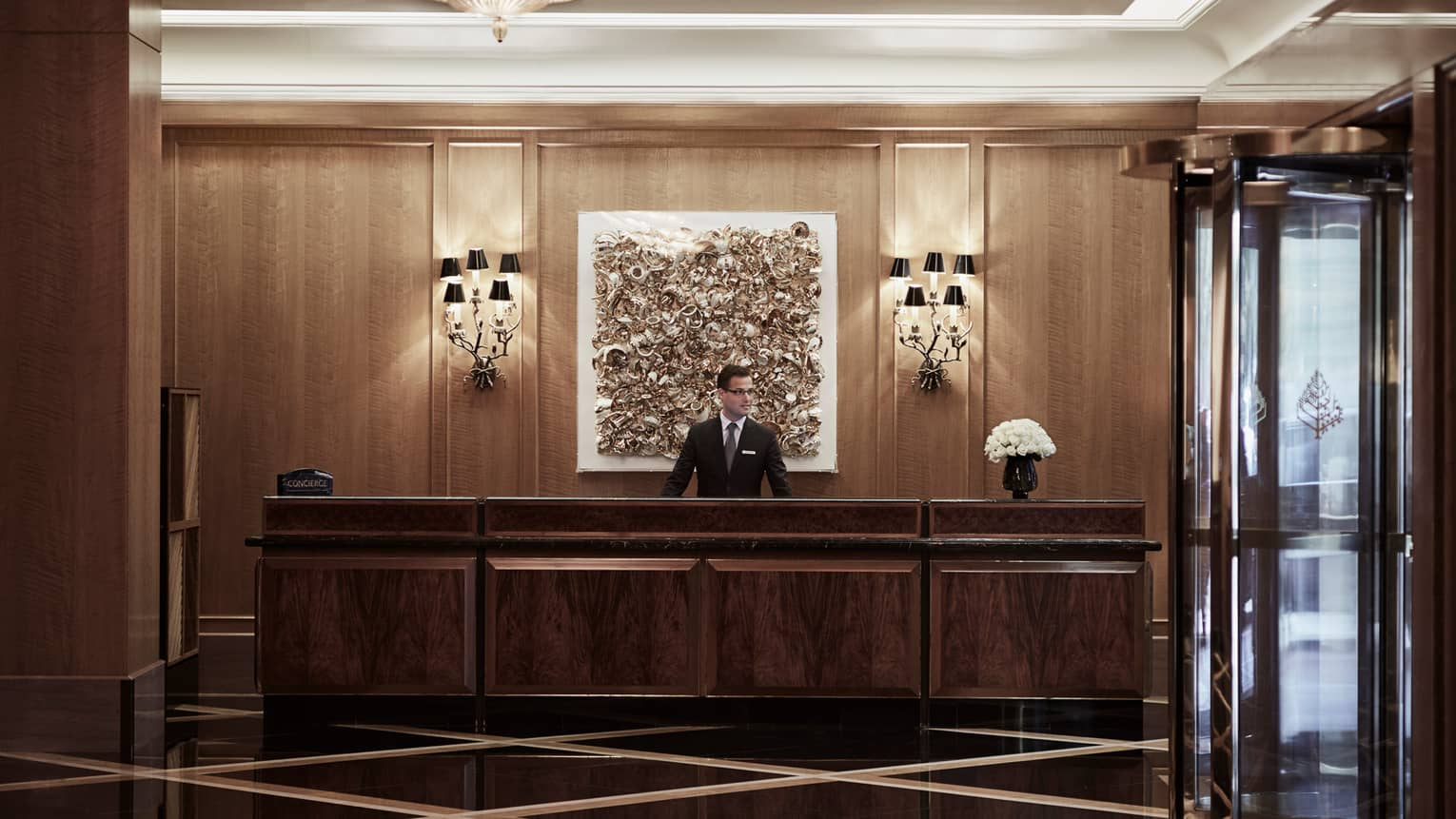 Concierge in suit and tie behind long wood desk in lobby beside glass revolving door