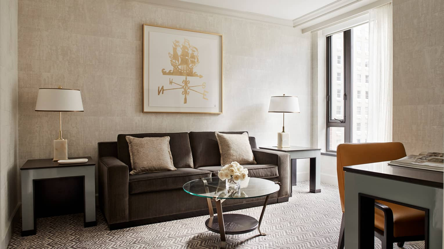 Four Seasons Executive Suite living room with dark grey sofa, beige pillows, framed gold print on wall, desk and sunny window