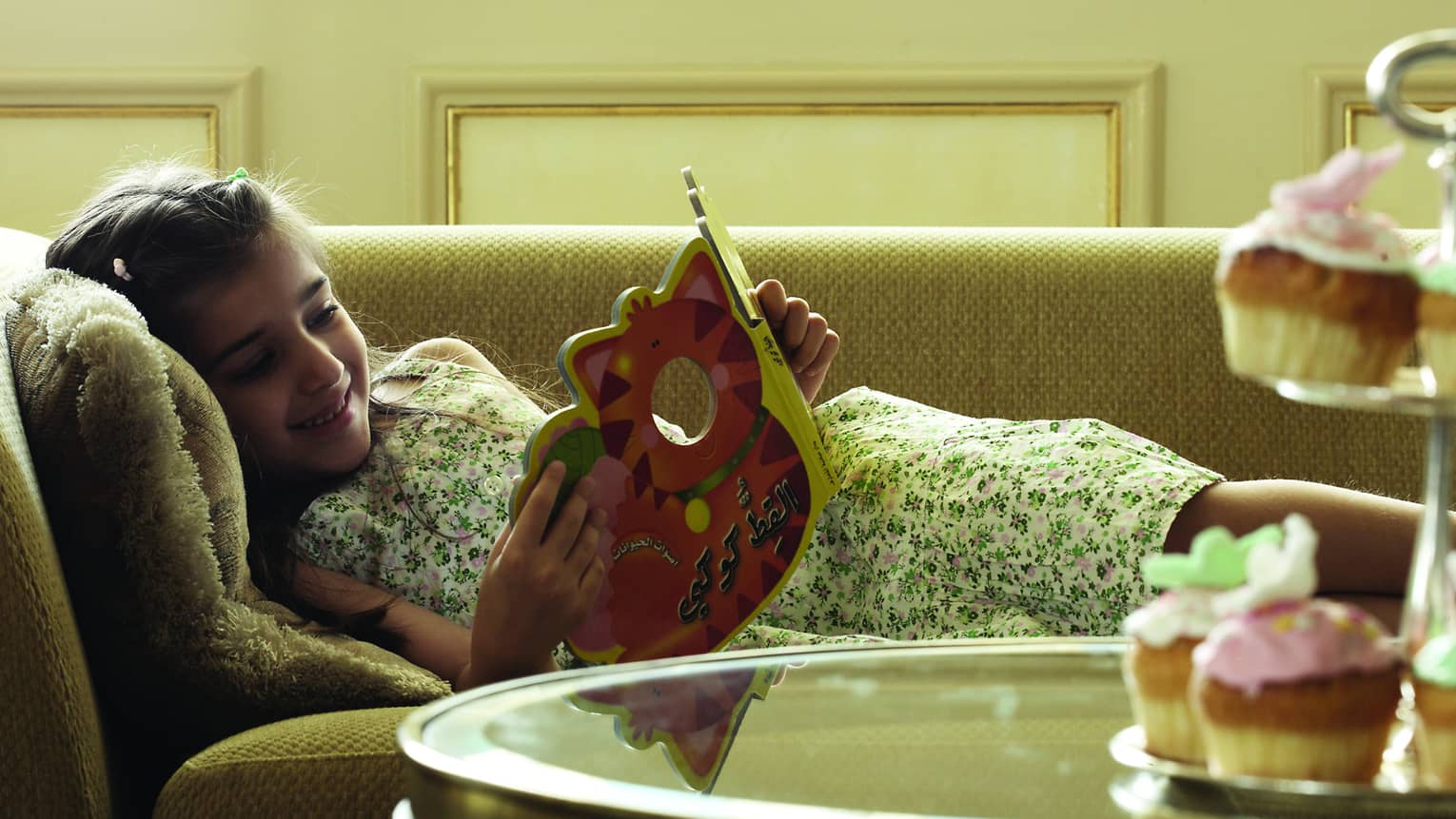 Smiling young girl lies on sunny sofa reading book
