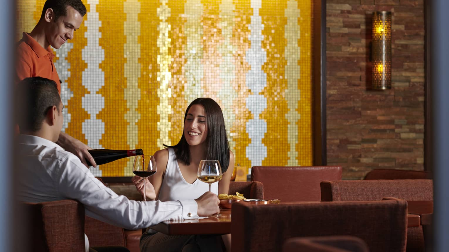 Couple enjoys a casual meal with wine at Aura