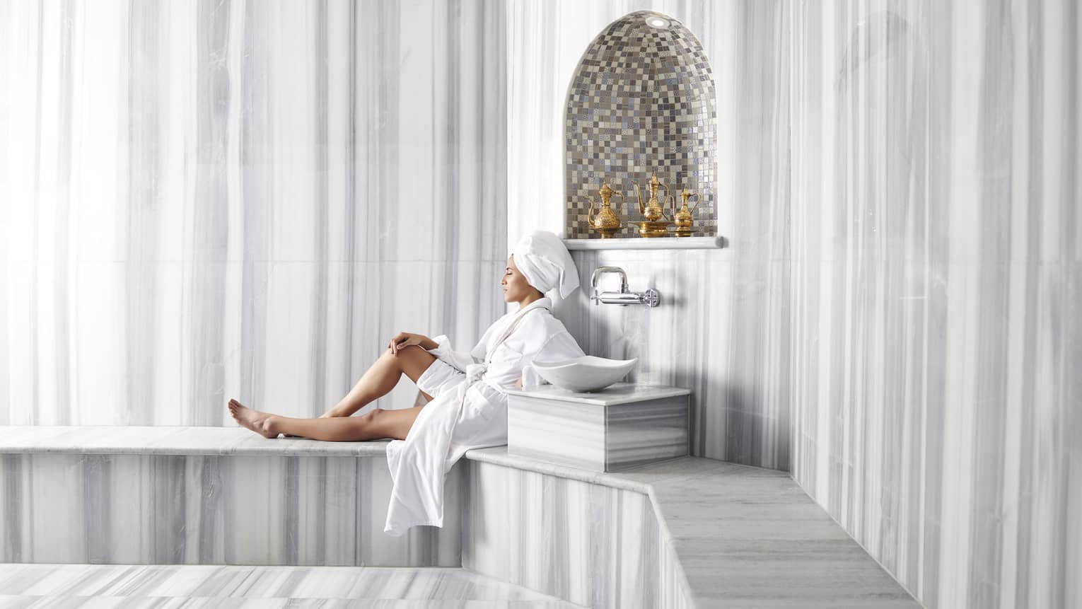 Woman wearing white bathrobe, towel around hair relaxes on bench in Hammam spa