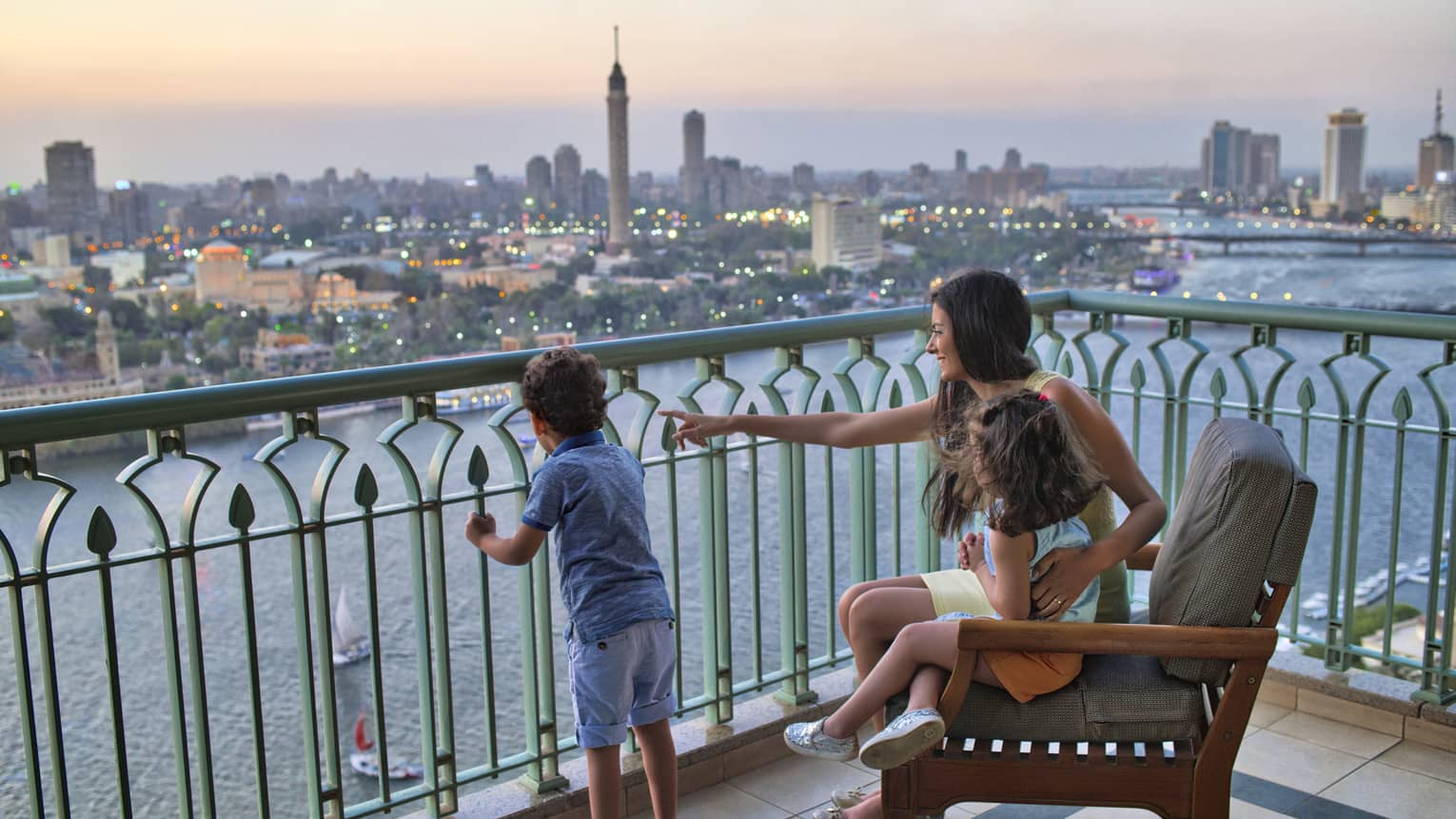 Woman seated with a young girl and beside a young boy standing, overlooking the Nile River and Cairo