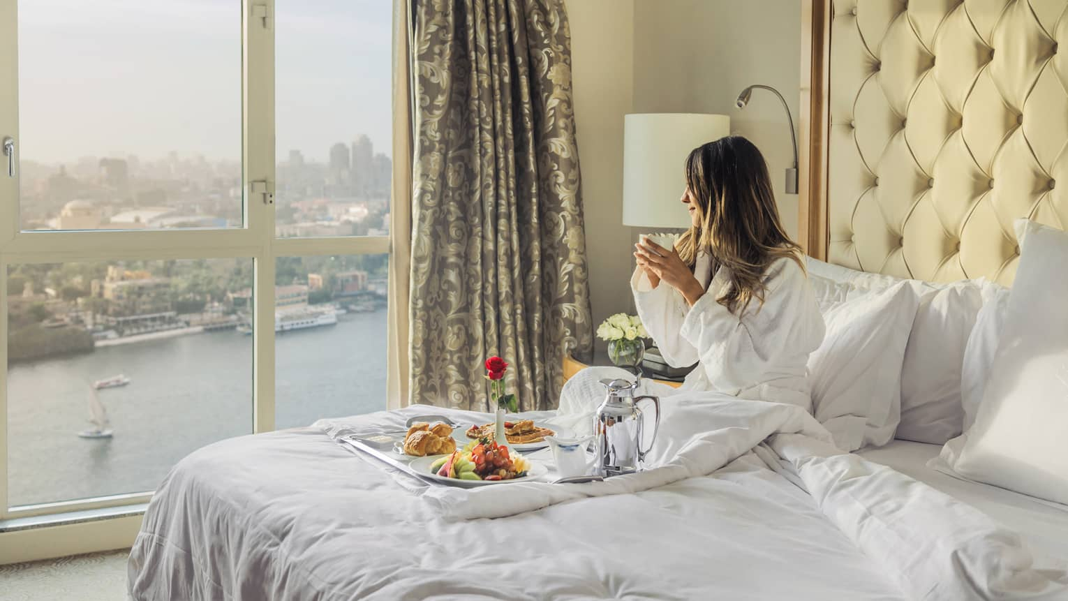Woman sitting on a bed with a tray of food, looking toward the Nile River and Cairo from the window