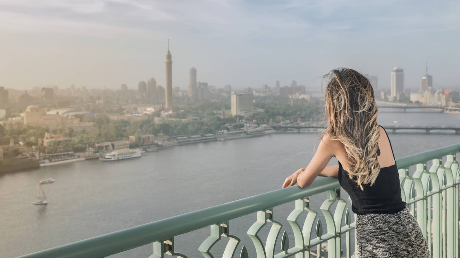 Woman with long blonde hair standing on balcony overlooking Nile River and Cairo