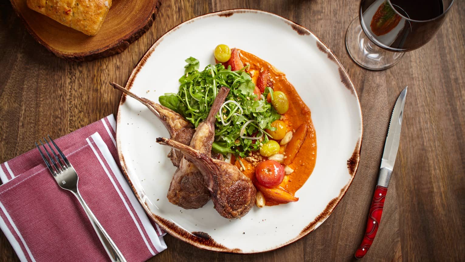 Looking down at white plate with seared lamb chops, greens and roasted vegetables in orange sauce