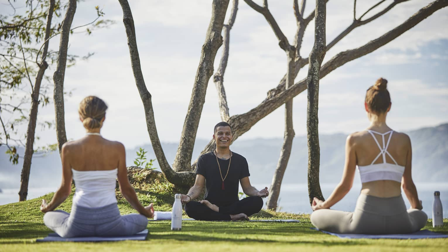 A yoga instructor leads two women in a class in front of hazy mountains