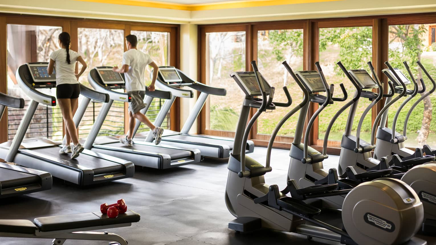 Man and woman run on treadmills near Fitness Centre window, row of cardio machines behind them
