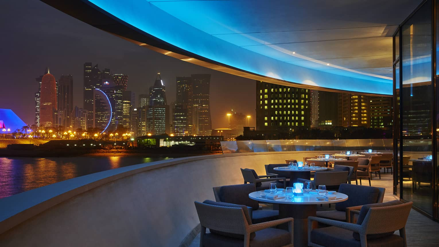 Curved Nobu restaurant patio with dining tables at night, skyline views, blue lights