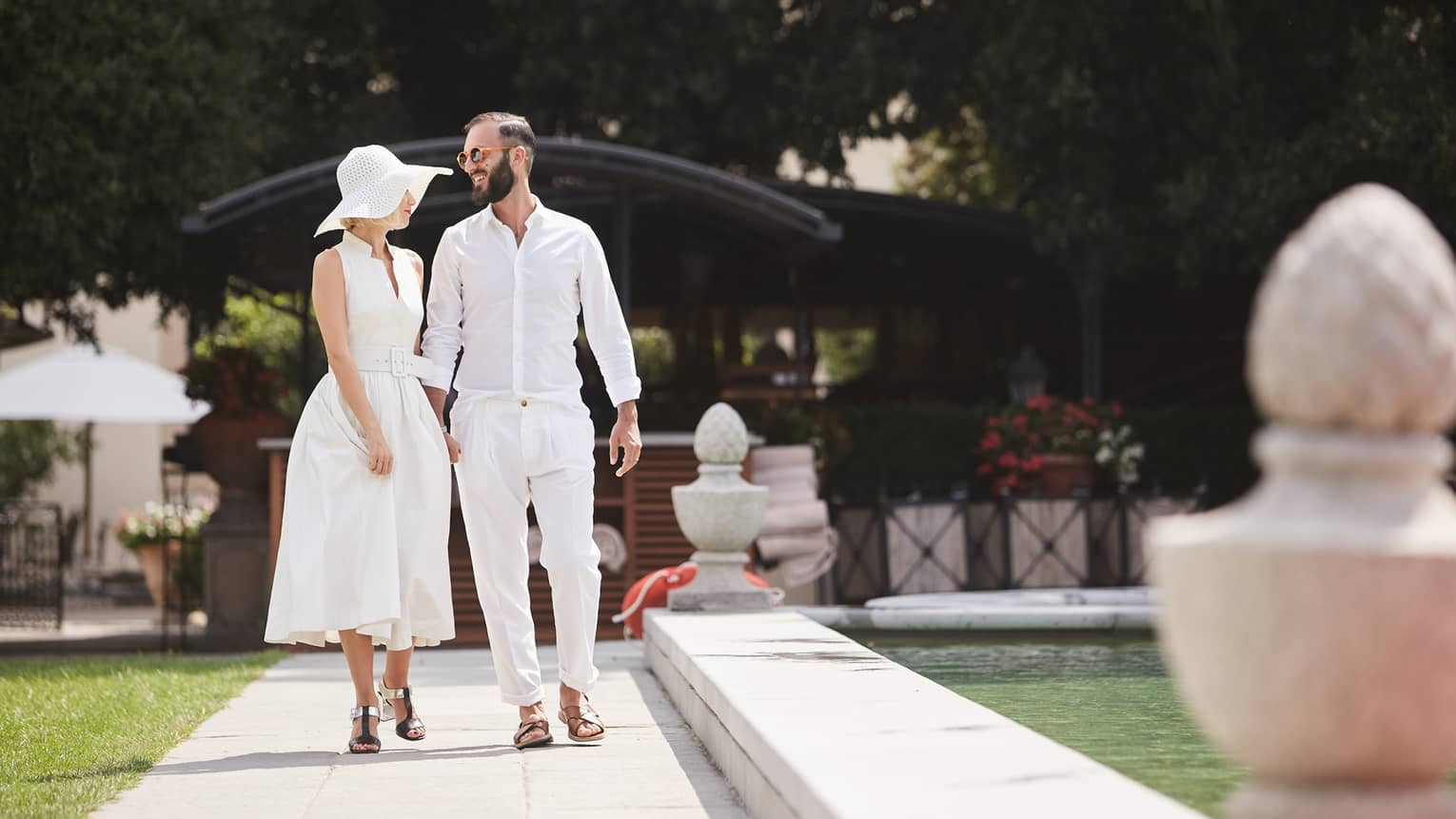 Man, woman wearing casual white cotton clothing stroll along sunny garden path by fountain