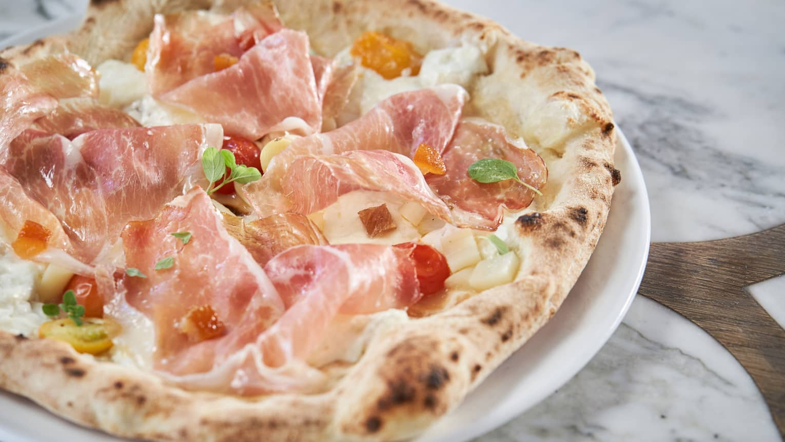 A signature pizza with prosciutto, cherry tomatoes and apricot