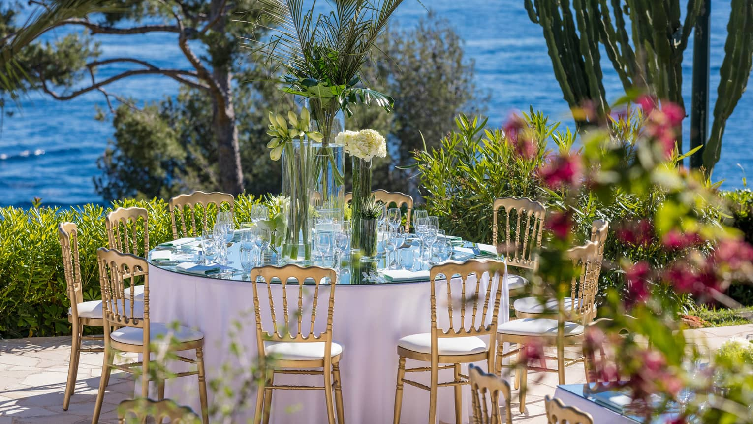 Small round outdoor wedding dining table on patio by sea